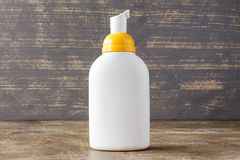 White dispenser on wooden background Royalty Free Stock Photography