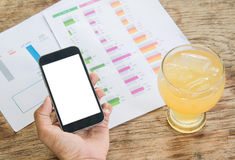 White display Smart phone in hand , Cold glass lemonade  , Graph. Data analysis placed on wooden floor Stock Photo
