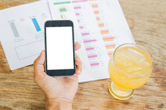 White display Smart phone in hand , Cold glass lemonade  , Graph. Data analysis placed on wooden floor Stock Images