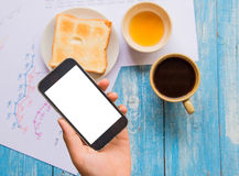 White display Smart phone in hand , Toast , Honey , Coffee cup. Royalty Free Stock Photo