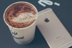 White Disposable Cup With Brown Liquid Inside Beside Gold Iphone 6 Royalty Free Stock Images