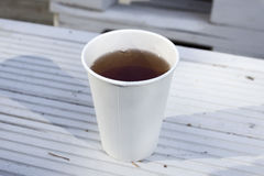 White disposable cup of tea or coffe on wood background. Lativa. White disposable cup of tea or coffe on white wood background. Latvia Royalty Free Stock Images