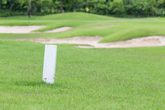 The white distance marker pole to inform range of golfing with b. Lurred green golf course Stock Images