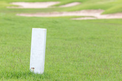 The white distance marker pole to inform range of golfing with b. Lurred green golf course Royalty Free Stock Image