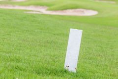 The white distance marker pole to inform range of golfing with b Royalty Free Stock Images