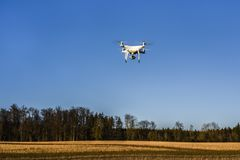 NEIDLINGEN, GERMANY - FEBRUARY 24, 2019: Front view of DJI Phantom 4 PRO quadcopter drone flying on blue sky royalty free stock photography