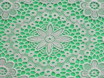 White doilie over light green background Royalty Free Stock Images