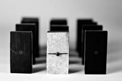 White Domino. Single white domino amongst black dominoes stock images