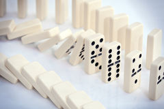White dominoes. Stacked white dominoes falling over Royalty Free Stock Photo