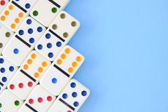 White dominos with brightly colored dots on blue background. Shot overhead with copy space royalty free stock photos