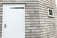 White door. With black hardware on side of weathered wood building Stock Image