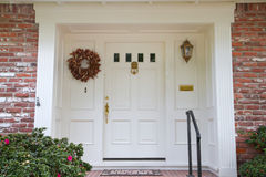 White door brick house. White colonial style door with brass fittings on a brick house Stock Photo