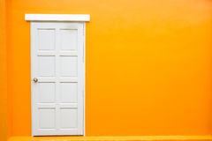 White door classic vintage on the color orange wall Stock Photos