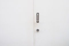 White door close with steel handle and key. Stock Photography