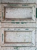 White door with cracked paint. Close up of two panels of old door with cracked and peeling white paint royalty free stock image