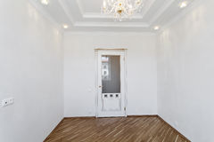 White door in empty room with white walls and ceiling Stock Photo