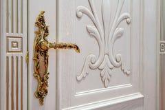 White door with golden lock. White door with golden antique lock and doorhandle close up view Royalty Free Stock Photo