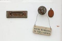 White door with notice - We're Working in the Garden. Stock Photography