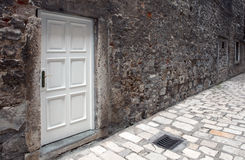 White door on ruined wall. New white door on old dirty wall in narrow paved street Royalty Free Stock Photography