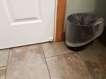 White door stopper with brown floor tile and garbage can. White door stop or door stopper with brown floor tile and garbage can stock images