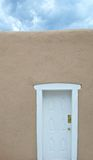 White Door - Stormy Sky. Front view of a wall with a white door and a stormy sky royalty free stock photo