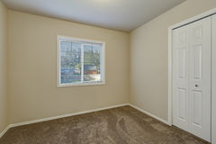 White doors closet and a window in empty beige room Royalty Free Stock Images