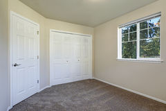 White doors closet and a window in empty beige room Royalty Free Stock Photography