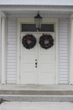 White doors with wreaths. Steps lead up to hanging Evergreen wreaths decorating the double doors of this white church building Stock Photo