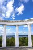 White doric columns blue sky with clouds. White doric columns against bushes river and blue sky with clouds Stock Photo