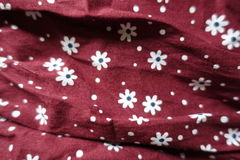 White dots and flowers print on maroon linen. Fabric stock image