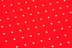 White dots on red cloth. Symmetric white dots embroidered on bright red texture Stock Photography