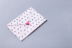 White dotted envelope with pink heart shaped figure. Hand crafted love letter for Saint Valentines Day celebration. Celebrate 14 February with handmade Stock Photography