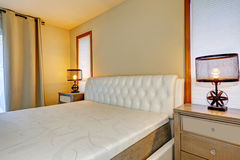 White double bed front view, with two lamps on bedside tables. Stock Photo
