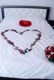 White double bed for the newlyweds with a white veil, a bouquet of red roses, red pad and the shape of the petals heart Stock Images