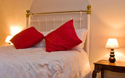 White double bed  and red pillows. Cosy country bedroom with white bedding and red pillows with bedside lamp Royalty Free Stock Photography