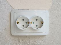 White double electrical socket in the room. Gray concrete wall on the background. Copyspace for text royalty free stock photography