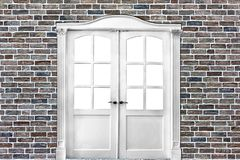 White double-leafed door of classical design in old brick wall. White double-leafed door of classica l design in old brick wall in grunge style stock image