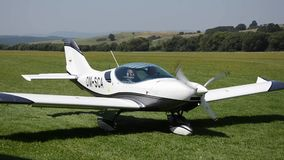 White double-seat propeller-driven PS-28 Cruiser airplane stops moving on grass landing strip in stock video