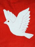 White dove on red fabric. Royalty Free Stock Images