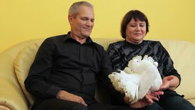 White Doves At An Elderly Couple. Mature couple holding two white doves stock footage
