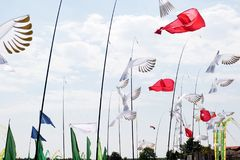 White doves and red flowers blowing in the wind at the kite festival at the storage sea geeste germany stock images