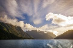 White Dragon in the Sky on a beautiful morning at Lake Manapouri. Glarious Sunlight in the Morning at Lake Manapouri with the clouds raising from the mountain Royalty Free Stock Photo