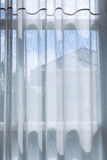 White drapery curtain hanging on the window Royalty Free Stock Photo