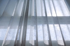 White drapery curtain hanging on the window. Interior decoration home, white drapery curtain hanging on the window with sun light in the morning day Stock Image