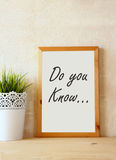 White drawing board with the question  do you know written on it against rustic textured wall Royalty Free Stock Images