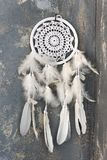 White dreamcatcher close up on dark gray textured background royalty free stock photography