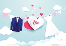 White dress and blue suit with heart sign hanging on cloud sky. White dress and blue suit with heart sign hanging on cloud sky background Royalty Free Stock Photos