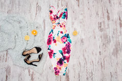 White dress in flowers, black shoes and halves of orange. Wooden background, fashionable concept Stock Photos