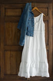 White Dress & Jacket Cabinet. White cotton dress and jeans jacket on wooden hanger on antique wardrobe Royalty Free Stock Images