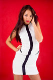 White dress on red. Brunette model white dessed on the red background Stock Images
